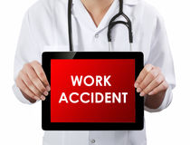 Doctor showing tablet with WORK ACCIDENT text. Stock Image