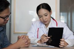 Doctor showing test result on tablet to patient at hospital. physician talk & give advice to man about his health at medical. Doctor showing test result on stock photography