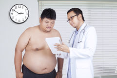 Doctor showing the test result to fat man Stock Photos