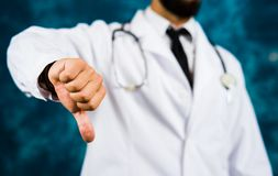 Doctor showing thumbs down close up Stock Photo