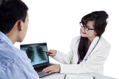 Doctor showing treatment result on laptop Stock Photos