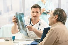 Doctor showing x-ray image to patient Stock Image