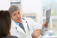 Doctor showing x-ray results to woman Royalty Free Stock Images