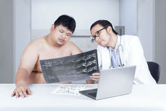 Doctor showing x-ray to overweight person Royalty Free Stock Photos