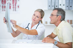 Doctor showing X rays to her patient Stock Photos