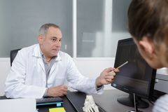 Doctor showing xray to patient in medical office. Doctor showing xray to his patient in medical office Royalty Free Stock Photography