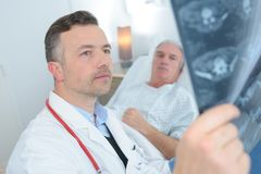 Doctor showing xray to senior patient in hospital Stock Image