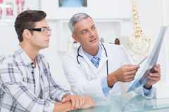 Doctor showing Xrays to his patient Stock Photos
