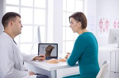 Doctor showing young patient her chest xray in his office at the hospital.  stock photography
