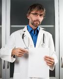 Doctor shows blank sheet of paper. To the clinic Royalty Free Stock Photos