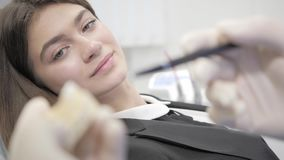 The doctor shows a cast of the jaw, fillings and implants. Young beautiful girl in the dentist chair at dental clinic. Portrait of a young beautiful girl in the stock video