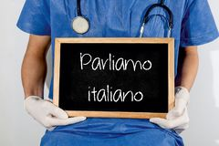 Doctor shows information on blackboard: we speak italian.  Medical concept stock photography