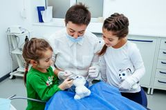 Treatment office children dentist teeth small girl teen red doctor new year discount woman clean clinic quietly comfortably. The doctor shows the little girls Stock Photography