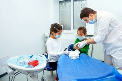 Treatment office children dentist teeth small girl teen red doctor new year discount woman clean clinic quietly comfortably. The doctor shows the little girls Royalty Free Stock Photography
