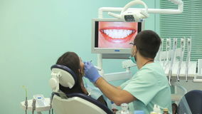 Doctor shows on the monitor the healthy teeth of the patient.  stock video