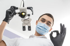 Doctor shows OK symbol. Happy dentist stands in the clinic and shows OK symbol. Man holds a glowing dental microscope with right hand. He wears a white uniform Royalty Free Stock Images