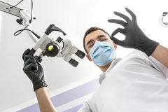 Doctor shows OK symbol. Pretty dentist stands in the clinic and shows OK symbol. Man holds a glowing dental microscope with right hand. He wears a white uniform Royalty Free Stock Photos