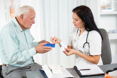 Doctor shows the patient how to use daily dose pills. Female doctor and senior man stock photo