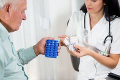 Doctor shows the patient how to use daily dose pills. Female doctor and senior man Royalty Free Stock Photography