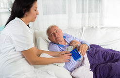 Doctor shows the patient how to use daily dose pills Stock Photography