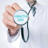 Doctor shows a stethoscope with the text health day Stock Image