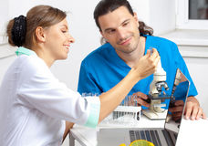 Doctor shows test tube. Doctor shows a researcher in the laboratory test tube Royalty Free Stock Images