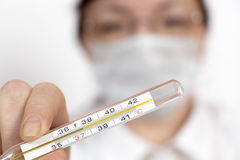 Doctor shows thermometer Royalty Free Stock Images