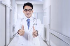 Doctor shows thumbs up in hospital corridor Stock Photos