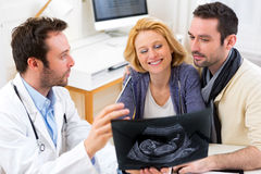Doctor shows an ultrasound to a young happy couple Stock Photos
