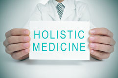 Doctor with a signboard with the text holistic medicine Royalty Free Stock Photos