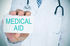 Doctor with a signboard with the text medical aid Stock Photo