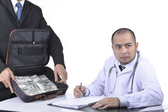 Doctor signed agreed reluctantly to a business agreement. Stock Images