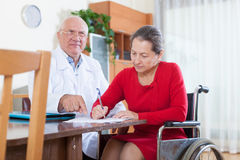 Doctor signing documents with   woman Royalty Free Stock Photography