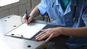 Doctor signs the document stock video footage