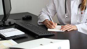 Doctor signs prescription stock footage