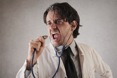 Doctor singing with his stethoscope royalty free stock images
