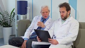 Doctor sits down near his colleague stock image