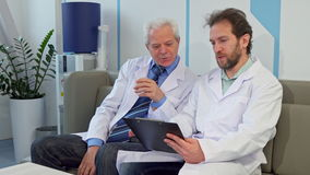 Doctor sits down near his colleague stock video