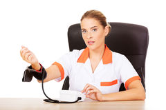 Doctor sitting behind the desk holding blood pressure gauge Royalty Free Stock Photo