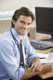 Doctor sitting at desk Stock Images