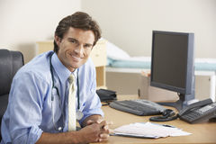Doctor sitting at desk Royalty Free Stock Images