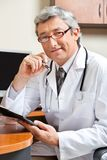 Doctor Sitting At Desk In Clinic stock images