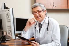 Doctor Sitting At Desk In Front Of Computer. Portrait of mature male doctor with clipboard sitting in front of computer at clinic Stock Photography