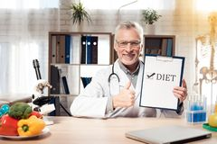Doctor sitting at desk in office with microscope and stethoscope. Man is giving thumbs up to diet. royalty free stock image