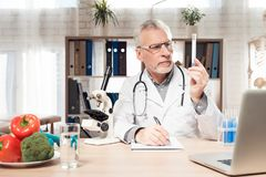 Doctor sitting at desk in office with microscope and stethoscope. Man is holding beaker. stock photo