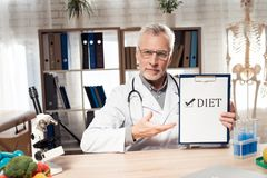 Doctor sitting at desk in office with microscope and stethoscope. Man is holding diet sign. royalty free stock photo