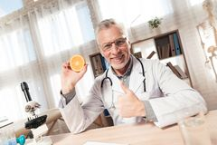 Doctor sitting at desk in office with microscope and stethoscope. Man is holding orange. royalty free stock photos