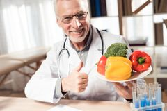 Doctor sitting at desk in office with microscope and stethoscope. Man is holding plate of vegetables. stock photo