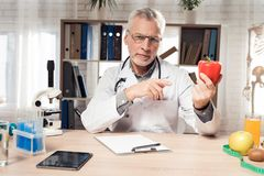 Doctor sitting at desk in office with microscope and stethoscope. Man is holding red pepper. stock photo