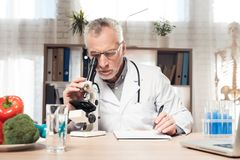 Doctor sitting at desk in office with microscope and stethoscope. Man is looking in microscope. Doctor in white robe sitting at desk in office with microscope Stock Photography